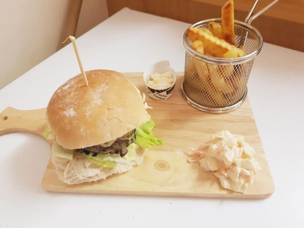 Beef burger with a side of coleslaw and chips with mayo