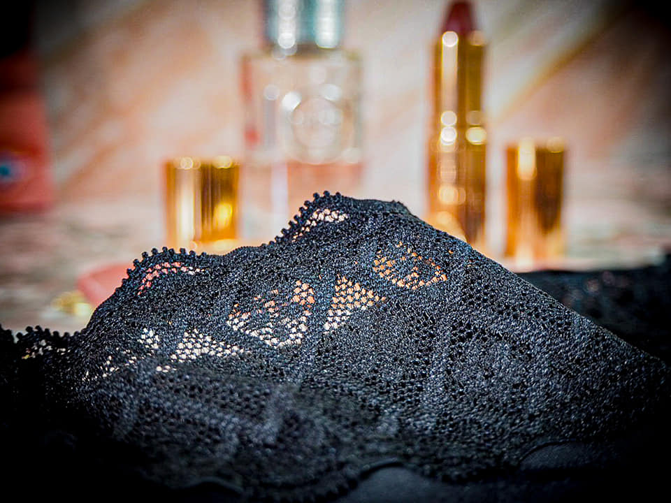 a close up of the lace trim on the underwear with two lipsticks and a perfume blurred in the background.