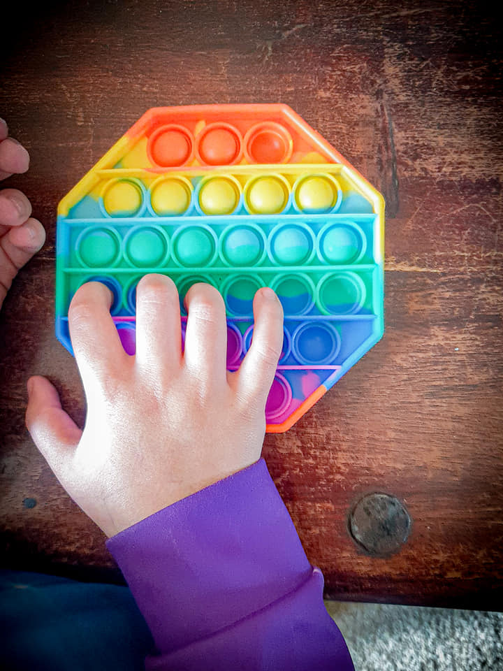 shaniah pushing the round poppers in her rainbow coloured hexagon shaped push popper.