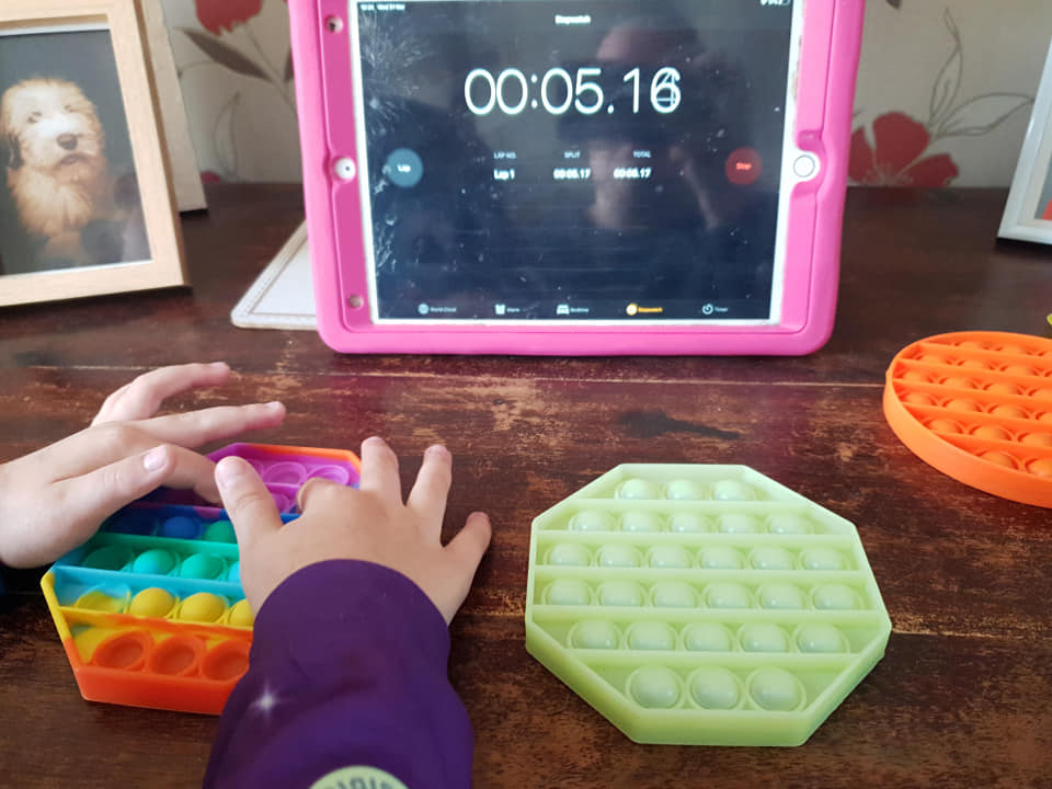 Shaniah is pushing the buttons on her push popper while her iPad is counting up in seconds in the background.